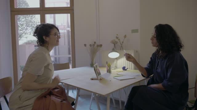 Zwei-Business-Frauen-haben-eine-Besprechung-oder-Vorstellungsgespräch-zusammen-mit-elektronischen-Gerät-auf-eine-lockere-und-freundliche-Besprechung