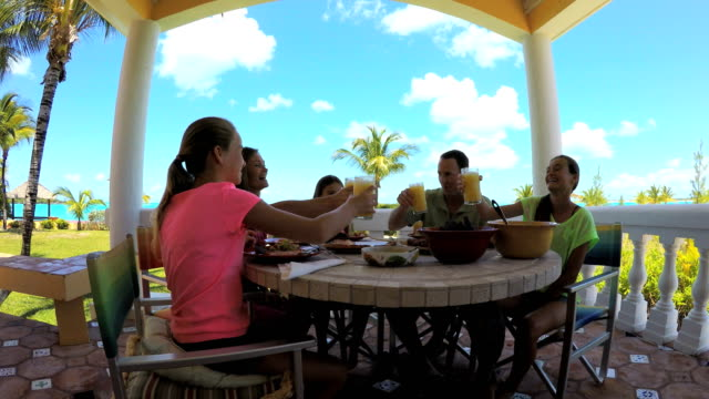 Caucasian-family-dining-on-vacation-beach-hotel-decking