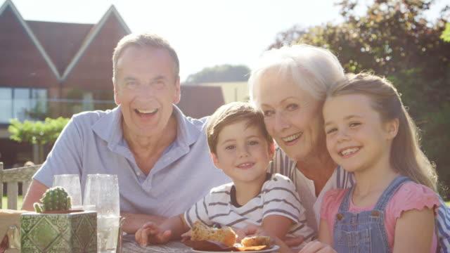 Portrait-Of-Grandparents-With-Grandchildren-Enjoying-Outdoor-Summer-Pub-Lunch