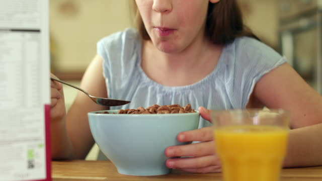 Close-Up-Of-Girl-Eating-Unhealthy-Bowl-Of-Sugary-Breakfast-Cereal-In-Kitchen