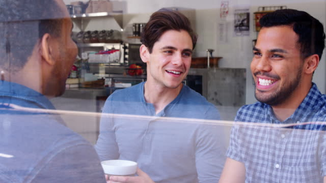 Three-male-friends-having-coffee-together-at-a-coffee-shop