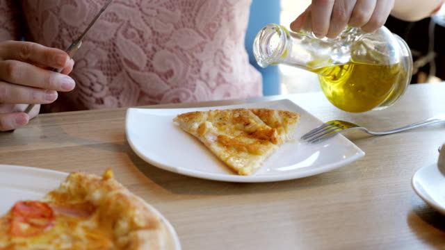 young-woman-in-a-cafe-is-eating-pizza-pouring-on-olive-oil