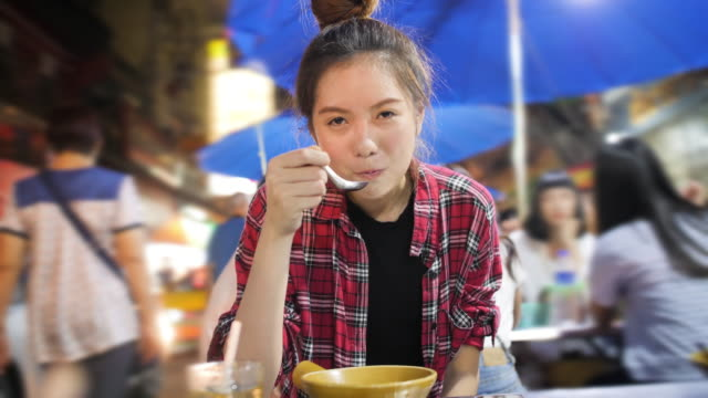 Young-attractive-asian-woman-enjoying-street-food-on-a-night-market-in-Thailand-Thai-food-concept-Asian-food-concept