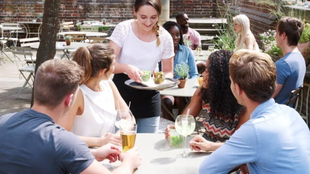 Group-Of-Friends-Meeting-For-Drinks-At-Outdoor-Tables-In-Restaurant-Being-Served-Snacks-By-Waitress