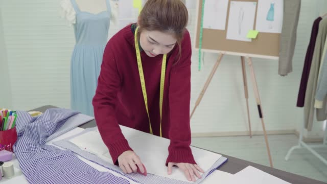 Professional-beautiful-Asian-female-fashion-designer-working-with-fabric-sketches-and-drawing-clothing-design-at-the-studio-Lifestyle-women-working-concept-