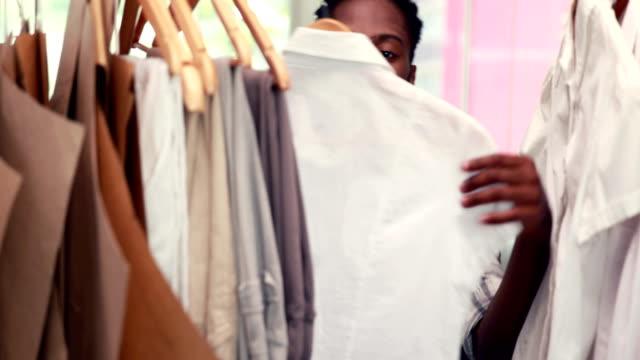 Hombre-diseñador-de-moda-mirando-en-rack-de-ropa
