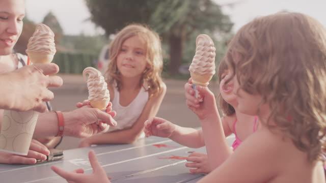 Un-padre-manos-de-un-helado-conos-un-sus-hijos-en-la-mesa-de-día-de-campo