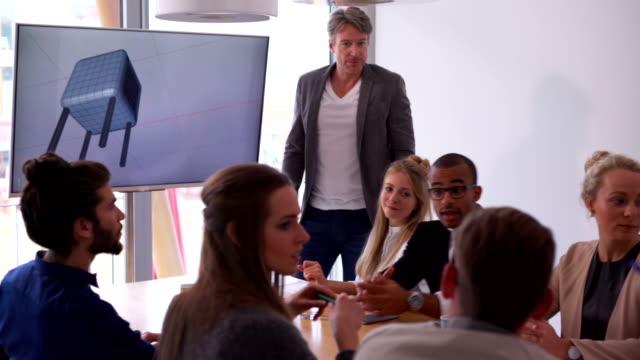 Multi-ethnic-team-members-discussing-presentation-in-board-room