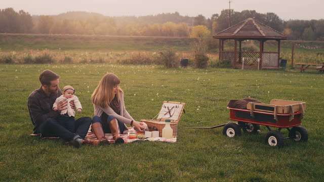 A-young-couple-on-a-picnic-with-their-baby-on-a-fall-day-wide-angle-with-lens-flare