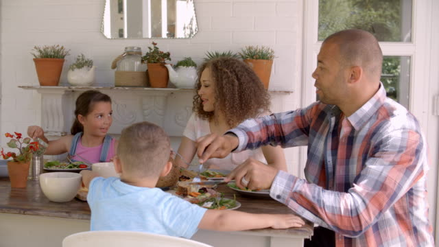 Family-At-Home-Eating-Meal-On-Outdoor-Verandah-Together