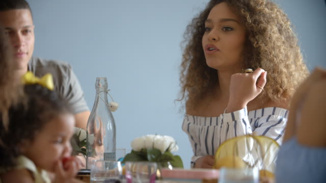 Adult-couple-and-young-girl-sit-talking-around-a-table