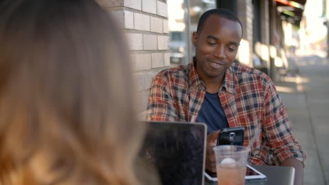 Mixed-race-couple-using-technology-outside-a-coffee-shop