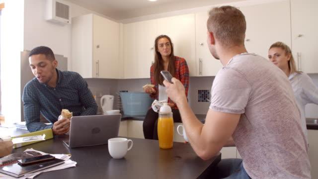 Estudiantes-relajantes-en-cocina-de-alojamiento-compartido