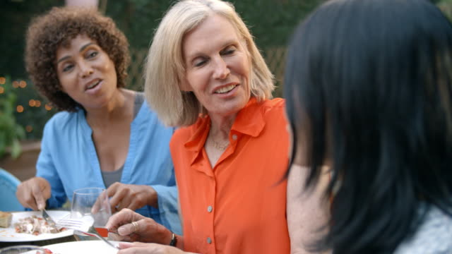 Mature-Female-Friends-Enjoying-Outdoor-Meal-In-Garden