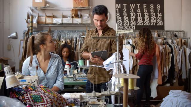 Colegas-que-hablan-en-un-taller-de-fabricación-de-ropa