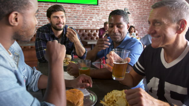 Group-Of-Male-Friends-Eating-Out-In-Sports-Bar-Shot-On-R3D