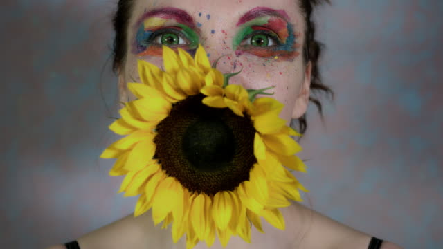 4k-Shot-of-a-Woman-with-Multicoloured-Make-up-With-Sunflower-(focus-on-face)