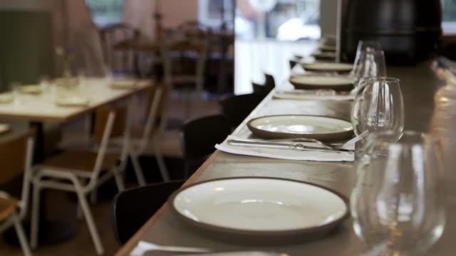 Place-settings-at-the-bar-of-empty-restaurant-tilt-shot