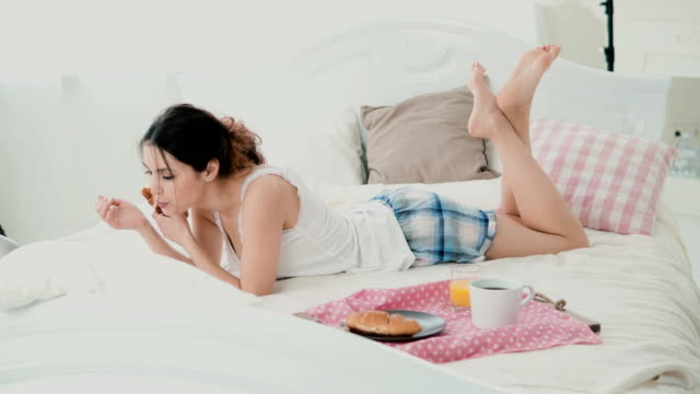 Beautiful-girl-lying-on-the-bed-in-morning-and-chatting-using-laptop-for-that-Young-woman-eating-croissant-and-typing