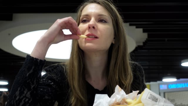 Young-woman-eating-hamburger-and-french-fries