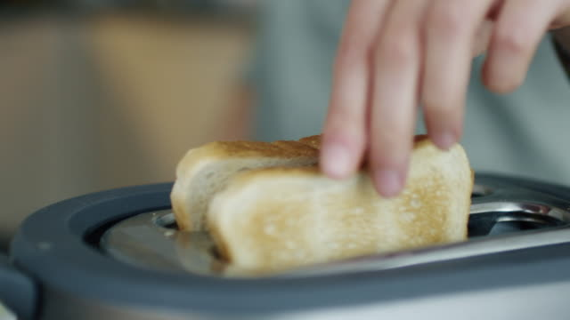 Close-up-of-a-Woman-Taking-Toasts-out-of-a-Toaster-