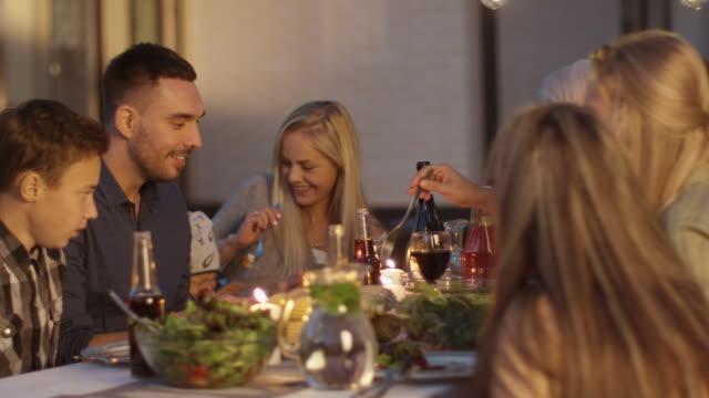Gruppe-der-Mixed-Rennen-Menschen-Spaß-Kommunizieren-und-Essen-beim-Outdoor-Family-Dinner