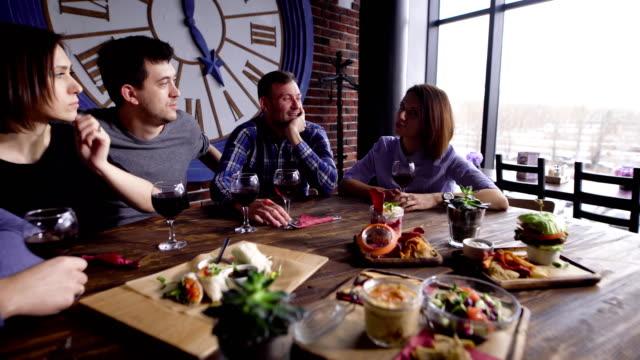 Fünf-Freunde-halten-Gläser-Rotwein-und-am-Tisch-serviert-mit-verschiedenen-Snacks-im-Restaurant-und-feiern-Männer-und-Frauen-verbringen-Freizeit-im-Café-in-der-Nähe-des-Fensters