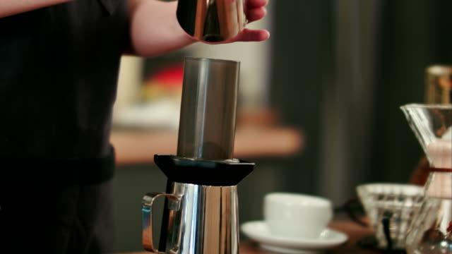 Barista-agregar-café-molido-y-verter-agua-caliente