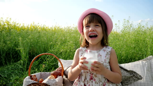 Pleasure-on-child-s-face-milk-advertising-Healthy-food-for-children-little-female-child-at-picnic-drinks-dairy-products-healthy-kid-drinks