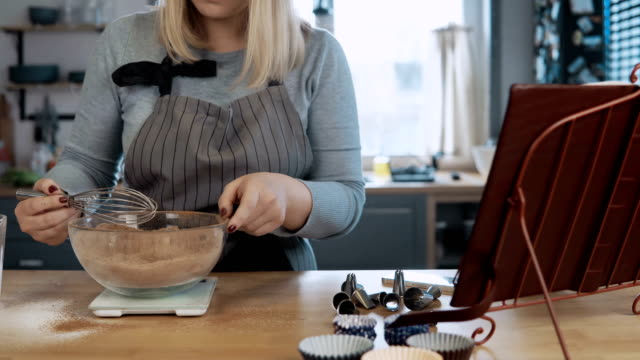 Young-beautiful-woman-mixing-ingredients-in-bowl-using-whisk-Attractive-female-looking-at-recipe-from-cooking-book