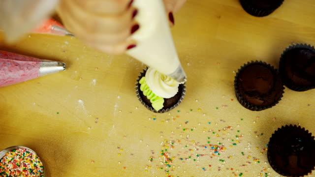 Draufsicht-der-jungen-Frau-Hände-Schokoladentörtchen-mit-farbigen-Sahne-verzieren-Weibchen-mit-dem-Spritzbeutel