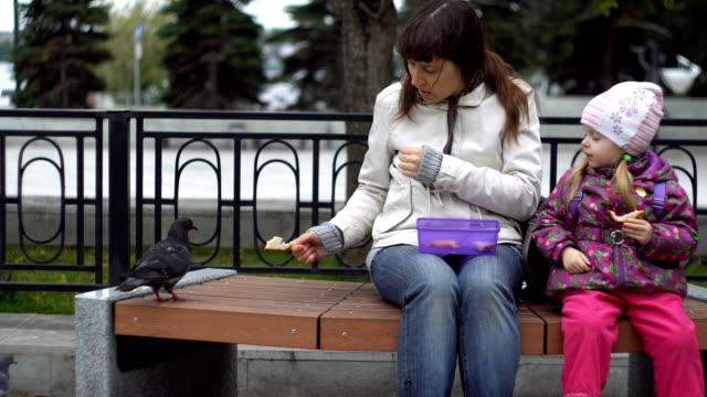 Madre-e-hija-comen-sándwiches-y-alimentan-palomas-en-un-día-frío-y-nublado-