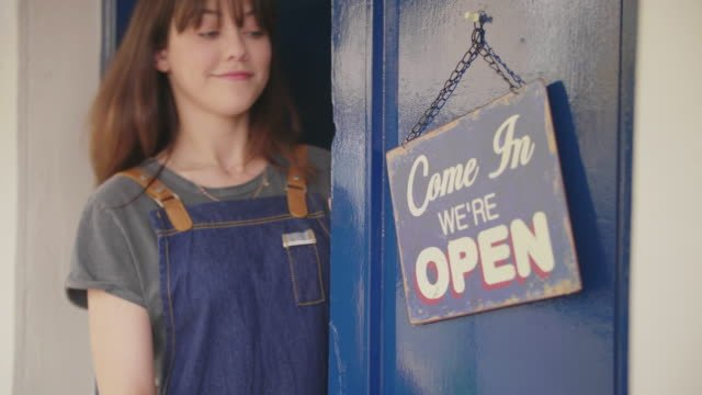 Deli-Owner-Turning-Sign-From-Open-To-Closed-On-Door