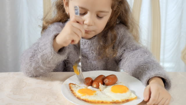 Cute-girl-eats-sausage-with-fork