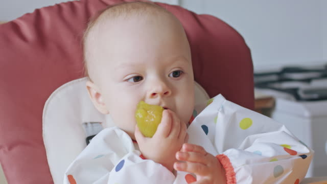 A-Baby-Girl-Eating-Plum-at-Home