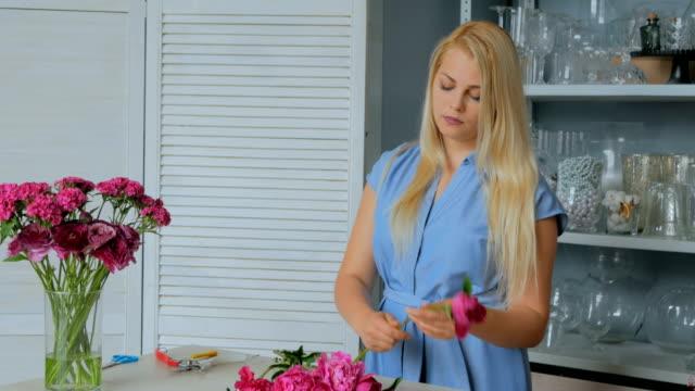 3-shots-Professional-floral-artist-sorting-flowers---pink-peonies-at-studio