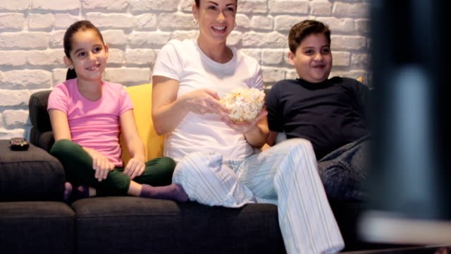 Alleinerziehende-Mutter-und-Kinder-vor-dem-Fernseher-in-der-Nacht