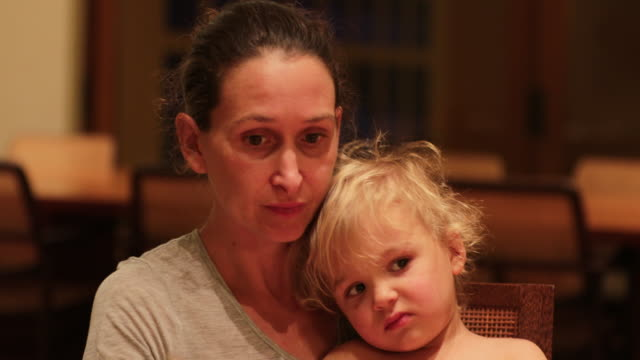 Baby-not-wanting-to-eat-dinner-Candid-real-life-expressions-of-mother-and-baby-together-at-dinner-table-Mom-preoccupied-that-toddler-boy-refuses-to-eat