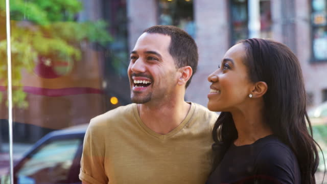 Smiling-couple-looking-at-clothes-in-shop-window-close-up