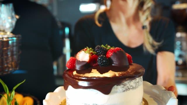 Waitress-Holding-Freshly-Baked-Cake-With-Buttercream-Frosting