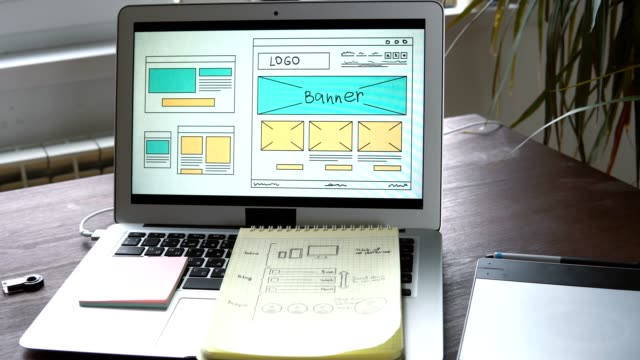 Web-developer-sitting-at-the-table-making-a-sketch-of-the-future-site-Working-remotely-from-a-home-office