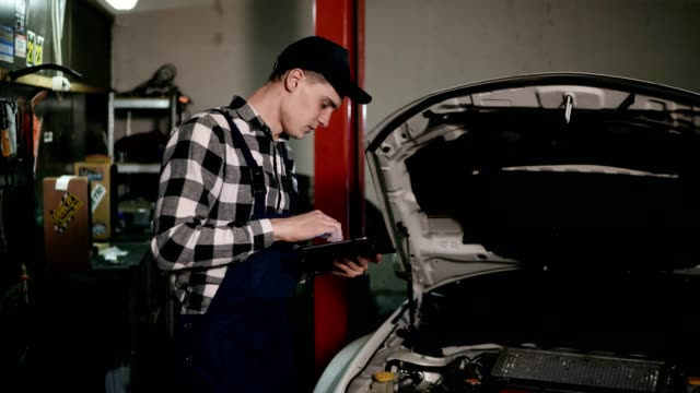 Mechanic-inspects-the-car-undercarriage-way-with-a-digital-tablet