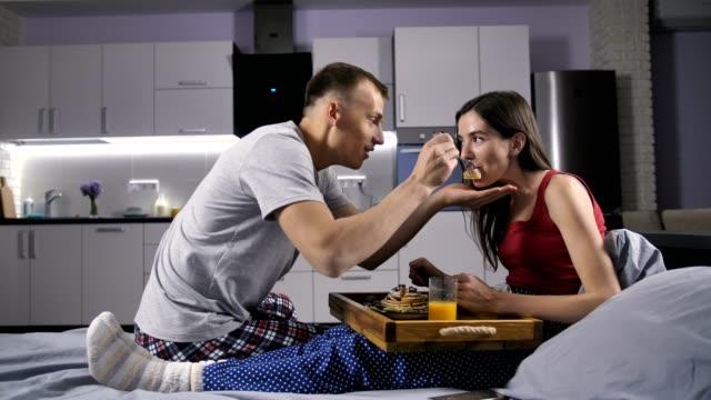 Hombre-que-alimentar-a-su-novia-con-desayuno-en-la-cama