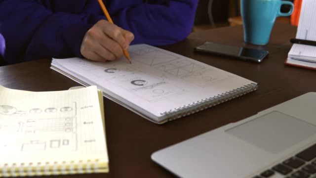The-application-developer-draws-sketches-in-a-notebook-Works-remotely-from-home-office