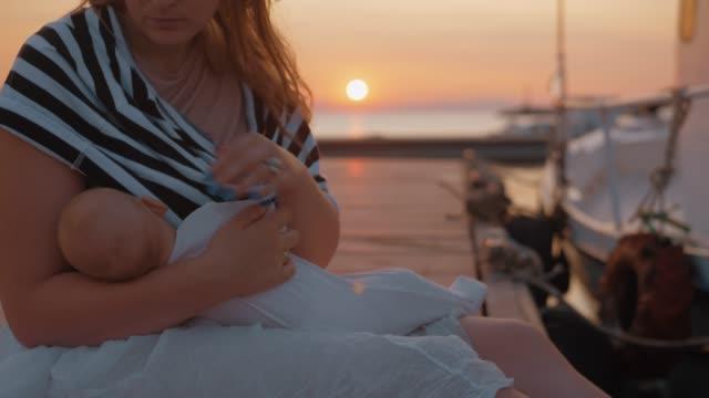 Mutter-Pflege-und-schmeichelnd-Babysitter-am-Pier-bei-Sonnenuntergang