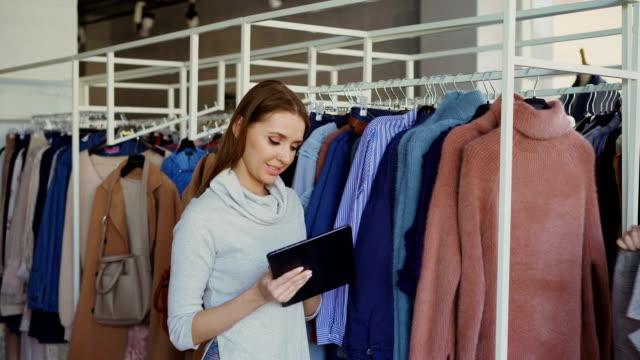 Joven-empresaria-está-utilizando-tablet-mientras-revisa-la-mercancía-en-su-tienda-de-ropa-Asistente-es-venir-con-ropa-y-pidiendo-Consejo-Empresario-es-dar-órdenes-