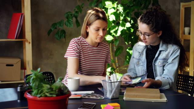 Kreative-Jungdesigner-sind-Fotos-aufmerksam-betrachten-und-diskutieren-sie-gemeinsam-am-Tisch-sitzen-Schwenken-Sie-Schuss-von-modernen-Loft-Stil-Büro-