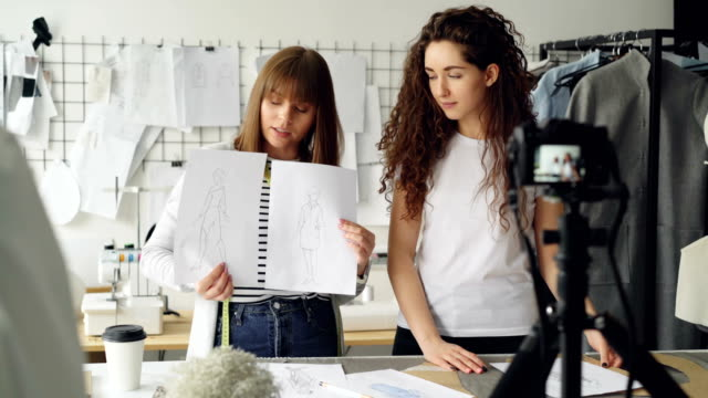 Young-pretty-women-fashion-designers-bloggers-are-recording-video-with-camera-about-sewing-new-garment-Girls-are-showing-sketches-and-templates-and-talking-together-