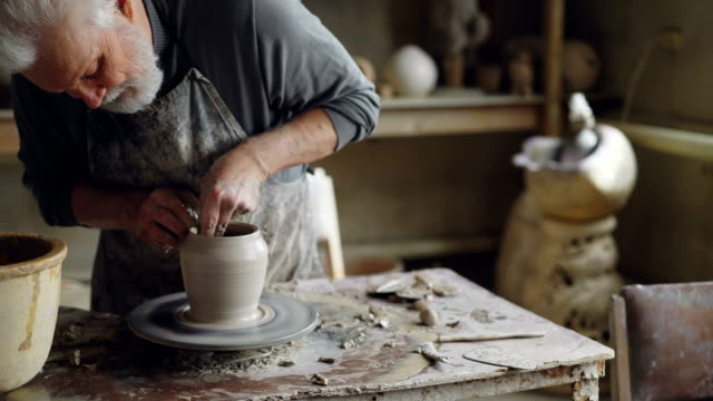 Experienced-ceramist-grey-haired-bearded-man-is-smoothing-molded-ceramic-pot-with-wet-sponge-Spinning-throwing-wheel-muddy-work-table-and-clayware-are-visible-
