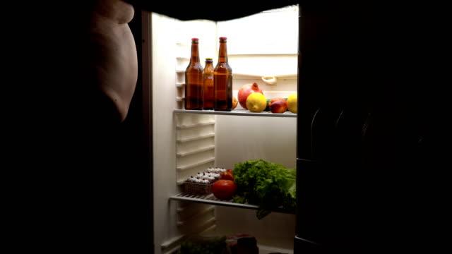 Un-hombre-gordo-toma-una-cerveza-en-la-nevera-